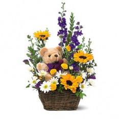 Panier de fleurs de printemps et un ours en peluche