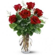 Six roses dans un vase en verre
